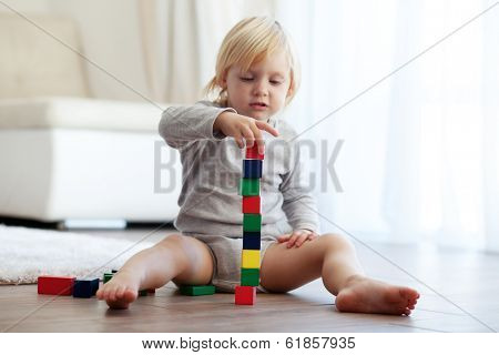 Toddler playing with wooden blocks at home