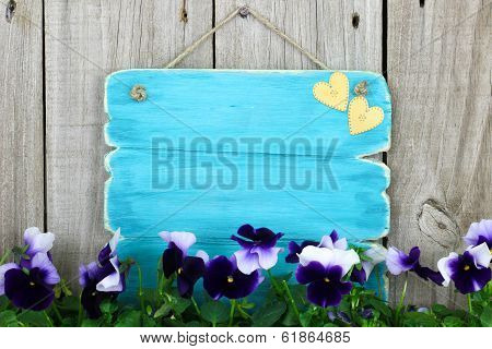 Antique blue sign with purple flowers (pansies)