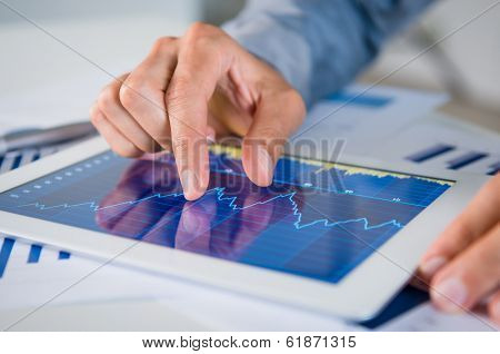 Close Up Of Businessman's Hand Analyzing Graph On Digital Tablet