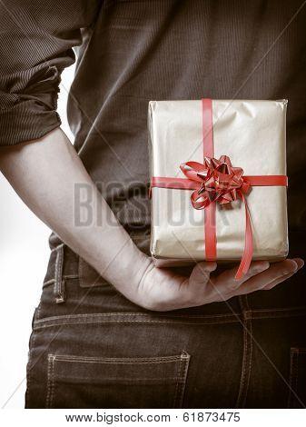 Holiday. Man Hiding Surprise Gift Box Behind Back