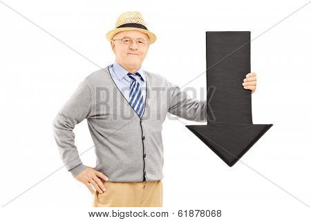 Smiling senior man holding a big black arrow pointing down isolated on white background