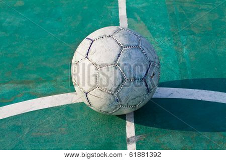 Old Used Football Or Soccer Ball On Cracked Asphalt