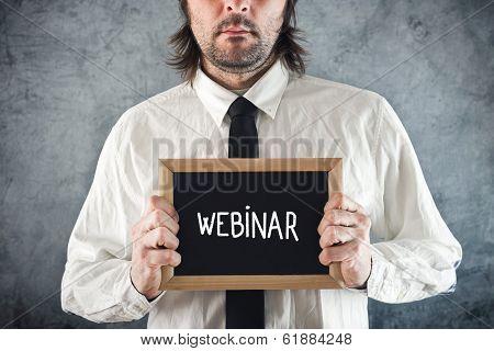 Webinar Concept. Businessman Holding Blackboard With Webinar Title
