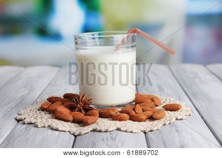 Almond milk in glass with almonds, on color wooden table, on bright background