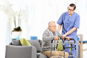 stock photo of male nurses  - Male nurse helping an elderly gentleman to stand up in a nursing home - JPG