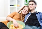 pic of nibbling  - Relaxed young couple watching television in their living room - JPG