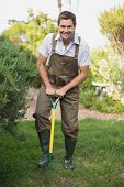 stock photo of dungarees  - Full length portrait of a happy young man in dungarees raking the garden - JPG