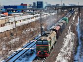 image of boxcar  - Goods train carries cargo along the track in the industrial area - JPG