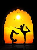 picture of natarajasana  - Two men in silhouette doing yoga difficult poses in old temple at orange sunset sky background - JPG