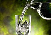 stock photo of jug  - jug of water poured into a glass - JPG