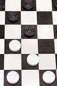 stock photo of draught-board  - above view of playing position on black and white draughts board - JPG