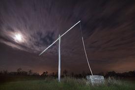 stock photo of shadoof  - Shadoof with moon at night illuminated with spotlight  - JPG