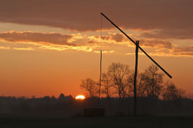 picture of shadoof  - Shadoof with orange sky and sun at sunrise - JPG