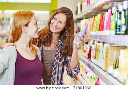 Happy mother and daughter shopping together in a supermarket drugstore