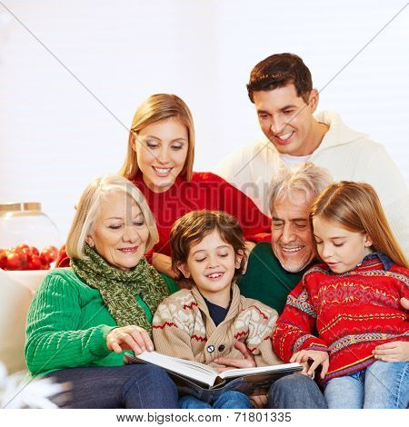 Happy three generation family reading story book at christmas