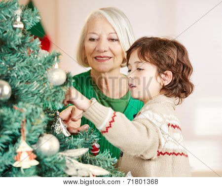 Grandmother and grandchild decorating christmas tree at home
