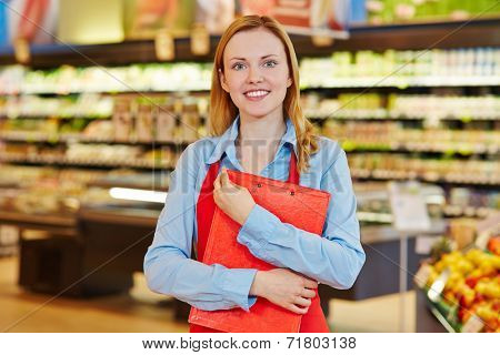 Young female supermarket employee holding a clipboard