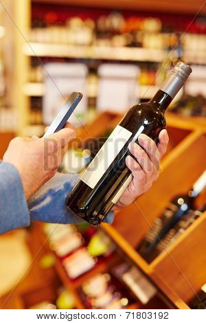 Price comparison with app in smartphone on bottle of red wine