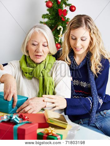 Woman helping senior citizen wrapping a gift for christmas