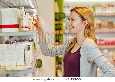 Young smiling woman buying cosmetics in a supermarket