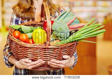 Hands carrying shopping basket with vegetables in a supermarket