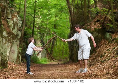 Father And Son Playing With Sticks On A Hike In A Beautiful Nature Park Between Scenic Rocks