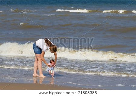 Young Mother And Her Newborn Daughter For The First Time On A Beach