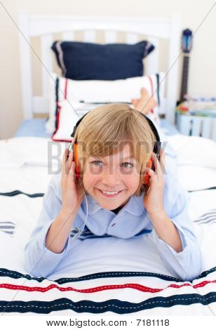 Relaxed Boy Listening Music Lying Down On Bed