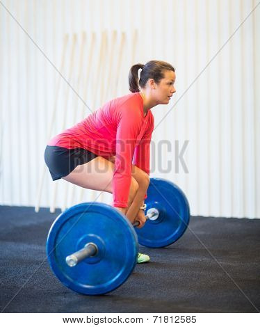 Side view of fit young woman picking barbell in gym