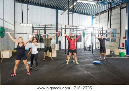 Crossfit instructors assisting athletes in lifting barbells in fitness box