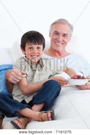 Cute Little Boy Taking Care Of His Grandfather