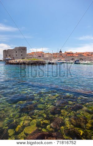DUBROVNIK, CROATIA - MAY 28, 2014: Small boats in city port with St. John fortress in background. Port is safe haven for many private boats of local citizens.