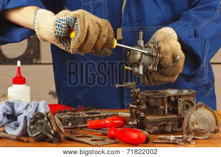 Serviceman repairing old car engine fuel pump