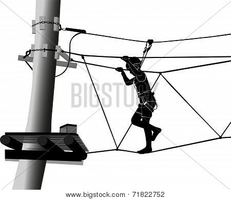 boy in adventure park on rope ladder