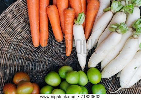 Fresh and healthy vegetables from Asian market, daikon white radish, carrots and tomatoes