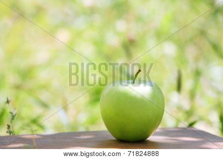 Juicy green apple on table, outdoors