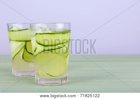 Two glasses of cucumber cocktail on napkin on wooden table on light background