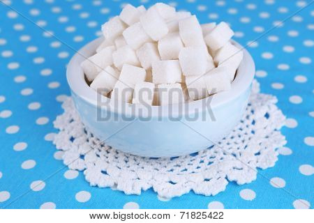 Refined sugar in color bowl on color fabric background