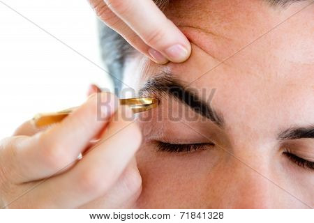 Man Removing Eyebrow Hairs With Tweezing.