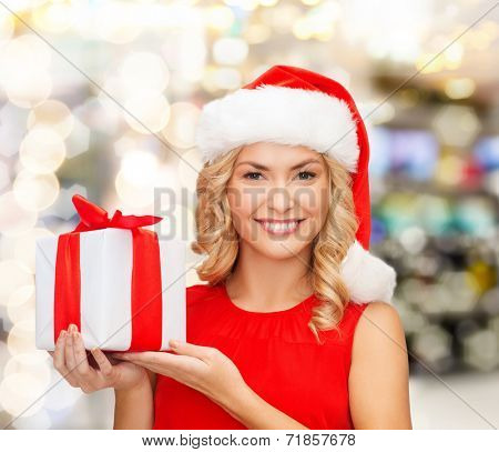 christmas, holidays, celebration and people concept - smiling woman in santa helper hat with gift box over lights background