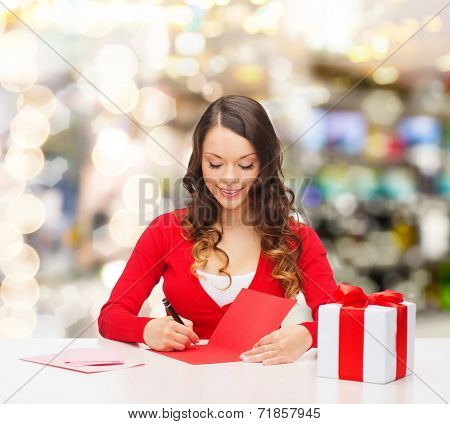 christmas, holidays, celebration, greeting and people concept - smiling woman with gift box writing letter or sending post card over lights background