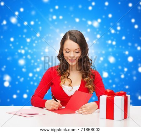 christmas, holidays, celebration, greeting and people concept - smiling woman with gift box writing letter or sending post card over blue snowy background