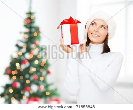 x-mas, winter, happiness, holidays and people concept - smiling woman in santa helper hat with gift box over living room and christmas tree background