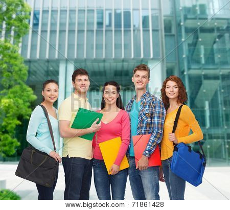 friendship, business, education and people concept - group of smiling teenagers with folders and school bags over campus background