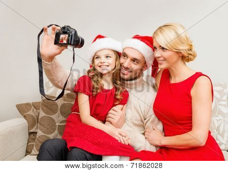 family, christmas, x-mas, happiness and people concept - smiling family in santa helper hats taking picture with photo camera