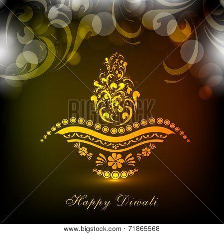 Golden floral design decorated illuminated lit lamp for Hindu community festival Happy Diwali celebrations.