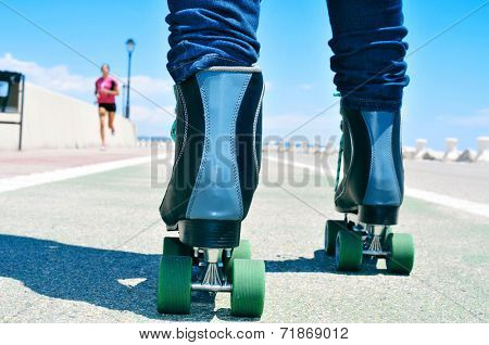 closeup of a young man roller skating on a no traffic road