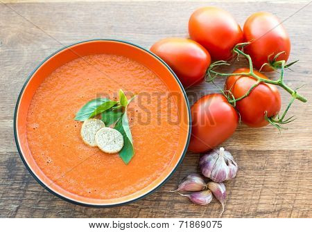 A bowl of tomato soup gaspacho with basil and crackers