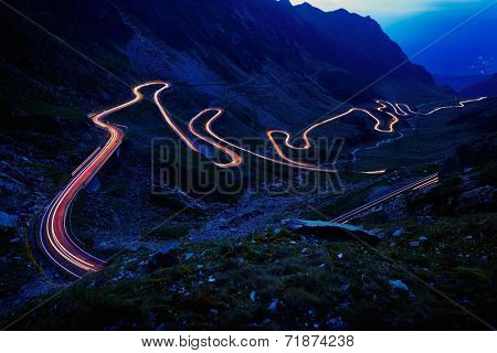 Landscape from the rocky Fagaras mountains in Romania in the summer evening with Transfagarasan winding road in the distance
