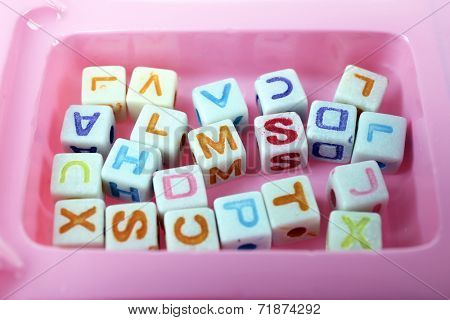 Multicoloured beads for children in a pink box